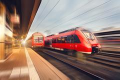 Modern high speed red passenger trains at sunset. Railway station Kuvituskuvat