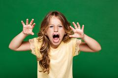 Young pretty girl frightening over green background Stock Photos