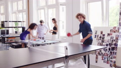 Young Business Executives interacting and man playing ping pong Stock Footage