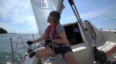 Sailing in the Baltic Sea. Yachtswoman raises the sail. Stock Footage