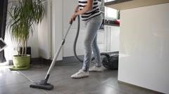 Homehelp vacuuming kitchen floor Stock Footage