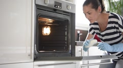 Young woman cleaning oven with fun attitude Stock Footage