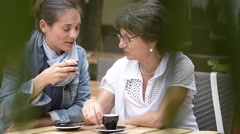 Senior woman with home carer having coffee together Stock Footage