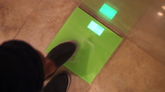 Man getting on a weighing scale Stock Footage