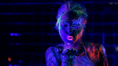 Girl in ultraviolet light blows pink fluorescent powder with palm Stock Footage