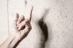 Middle finger concrete wall - stock photo