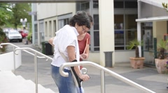 Home carer helping disabled woman getting down the stairs Stock Footage