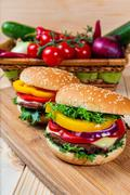 Homemade hamburger with fresh vegetables on cutting board Stock Photos