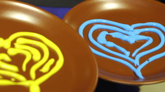 Brown plate with paint blue and yellow heart symbol Stock Footage
