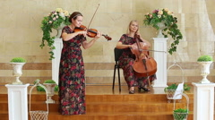 Duet of Cellist and violinist plays music on the stage. Stock Footage