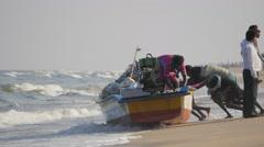 Fishermen pushing boat in sea,Chennai,India Stock Footage