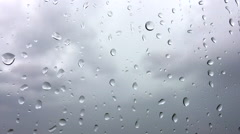 Raindrop on window with lightning, grey sky background Stock Footage