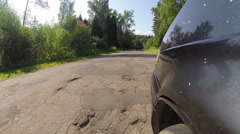 The vehicle starts up and begins to move along the road with bad asphalt Stock Footage