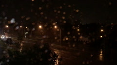 Raindrop on window with lightning night time, blur bokeh lights background Stock Footage