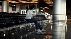 Girl stare at phone, sit at empty departure lounge, wait for flight Stock Footage