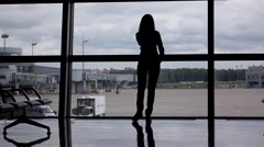 Silhouette of girl talk on phone, stand against full height window at airport Stock Footage