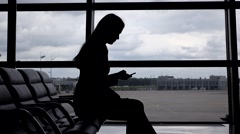 Sitting girl silhouette, wait with smartphone at airport terminal against glass Stock Footage