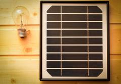 small solar panel and a light bulb - stock photo