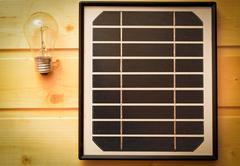 Small solar panel and a light bulb Stock Photos