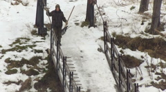 Male With Shovel Coming Down to the Bridge From From the Slippery Pass in Stock Footage