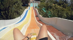 FPV: Man sliding down extreme fast water slide toboggan on a fun summer day Stock Footage