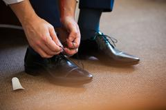 Man ties his shiney new black leather business shoes Stock Photos