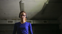 Beautiful young woman with the gun on an indoor shooting range. shoots a gun Stock Footage