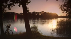 Backlit summer scene at the lake with camera pan Stock Footage