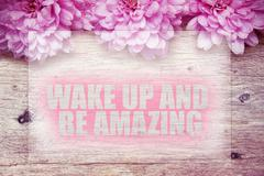 Pink flowers on wooden with word Wake up and be amazing Stock Photos