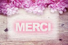 Pink flowers on wooden with word Merci Stock Photos