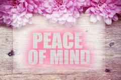 Pink flowers on wooden with word Peace of mind Stock Photos