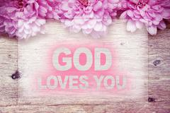 Pink flowers on wooden with word GOD LOVES YOU Stock Photos
