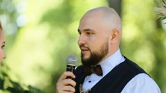 Handsome elegant bald groom taking vows at the outdoors wedding ceremony Stock Footage