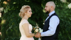 Wedding: beautiful young bride and groom standing in a park outdoors holding Stock Footage