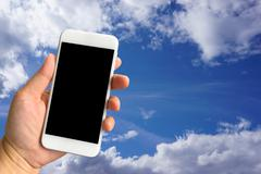 Woman hand holding smartphone against blue sky background, travel concept Stock Photos
