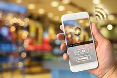 Woman hand holding smartphone against blur bokeh of shop background VDO ads c Stock Photos