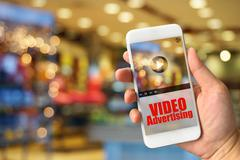 Woman hand holding smartphone against blur bokeh of shop background VIDEO Adv Stock Photos