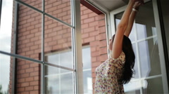 Beautiful young woman in nightie is waking up and stretching the open window. Stock Footage