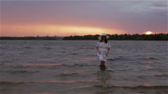 A woman coming out of water at sunset. Stock Footage