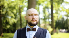 Handsome groom in a white shirt, brown bow tie and vest walking in the summer Stock Footage