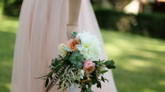 Beautiful wedding bouquet with white and pink roses in hands of bride walking Stock Footage