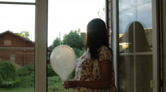 The middle aged woman is standing at open balcony doors with balloon in hands. Stock Footage