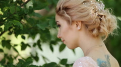 Charming blond woman in her tan dress looking over her shoulder with an owl - stock footage