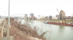 Pan of bridge, river, and tug boat with dredger and crane (HD) Stock Footage