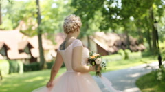 Charming young blonde bride with bouquet in romantic lace wedding dress dancing - stock footage