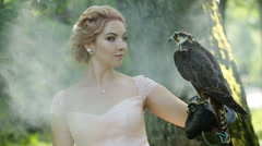 Gorgeous Women Outdoors. Fashionable Girl with Bird of prey posing in green Stock Footage