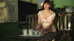 The middle aged  woman is drinking tea sitting on a bench in the sunset. - stock footage