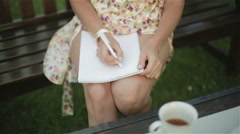 Female hand writing a letter on the paper on the nude sunburned knees. Stock Footage