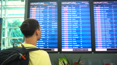 Male traveler backpacker looking at airport schedule - stock footage