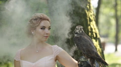 Portrait of a beautiful woman wearing with big eagle falcon on arm at foggy Stock Footage